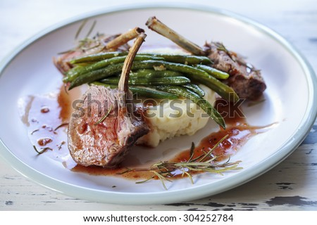 Lamb rack with mash potatoes, green beans and red wine jus - stock photo