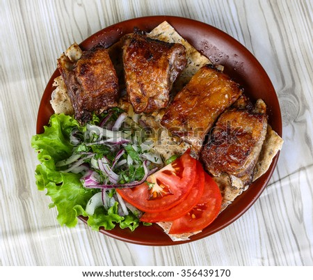 Lamb ribs bbq with tomato, bread, salad leaves and onion