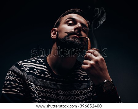 Lamber like male model with moustache and beard smoking pipe and showing dominant attitude with his body language