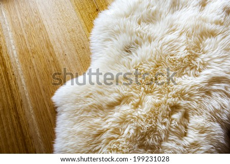 Lambs wool sheepskin on a timber floor - stock photo