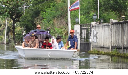 LAMLUKKA (PATHUMTHANI), THAILAND – CIRCA NOVEMBER 2011 – An unidentified rescue team in a boat transports a group of unidentified people through a flooded road circa November 2011 in Lamlukka.