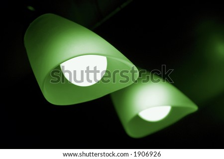 Lamp and its reflection in a mirror, on dark background, shallow dof, place for inscription or slogan. Green variant. - stock photo