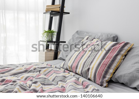 Lamp, books and green plant on a shelf decorating a modern bedroom. - stock photo