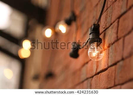 Lamp garland on brick wall background, closeup