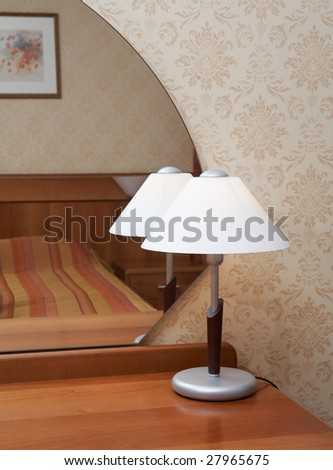 Lamp in front of mirror in a modern bedroom