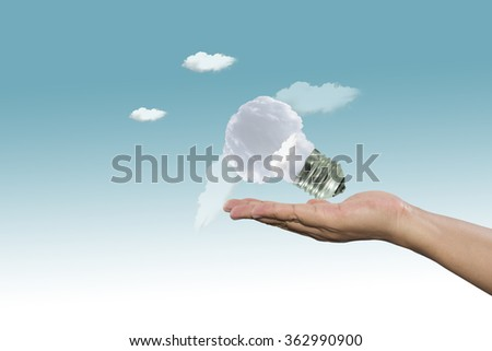 Lamp made of clouds in hand on sky. Ecology conception.Blue sky. - stock photo