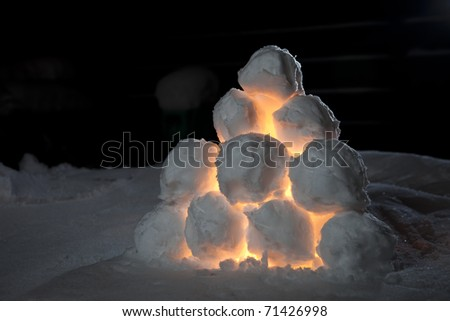 Lamp made of snowballs shining in a dark winters night - stock photo