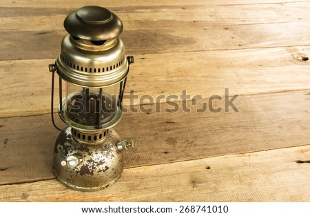 Lamp oil lantern retro on wooden background - stock photo