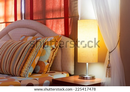 Lamp on a night table next to a bed, cozy living bedroom - stock photo