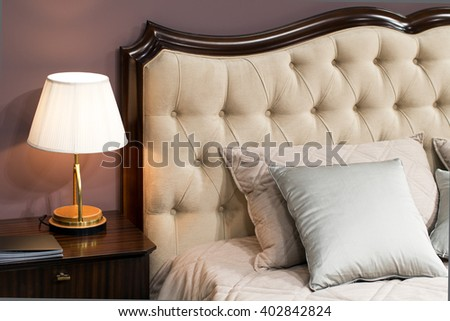 Lamp on a night table next to upholstery bed with pillows - stock photo