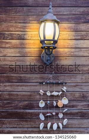 Lamp on Wood Texture And Hanging Seashells - stock photo