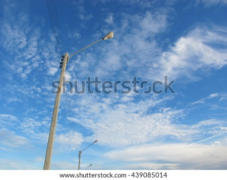 Lamp post and blue sky.Blue sky on the afternoon of the day. A fluffy white clouds and bright atmosphere. - stock photo