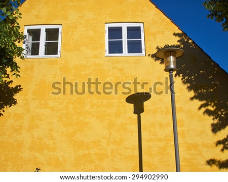 Lamp Post Street Road Light Pole casting a shadow over a yellow house - stock photo