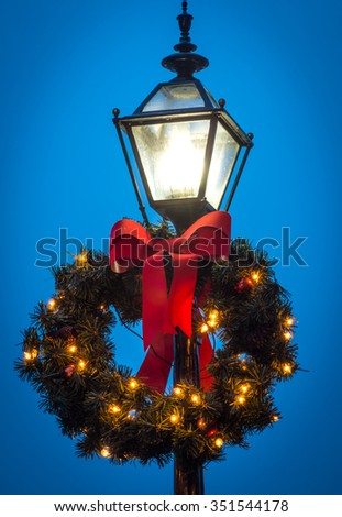 Lamp Wreath - vertical color image of illuminated street lamp with Christmas wreath against dark blue sky. - stock photo