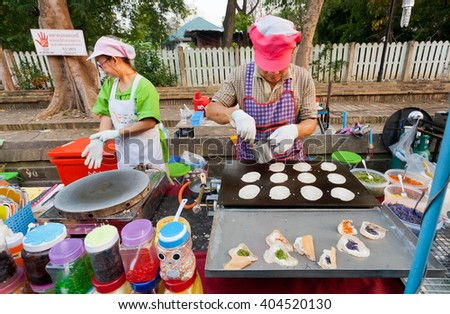 LAMPANG, THAILAND - FEB 19: Women cooking small pancakes  on a stove during street fair with fast food court on February 19, 2016. Population of Lampang is near 59,000 people - stock photo