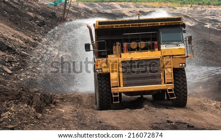 LAMPANG, THAILAND - JUNE 26:  Big yellow mining truck Sprinkle water Reduce dust, June, 26, 2014 in Lampang, Thailand - stock photo