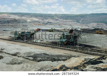 LAMPANG, THAILAND-MAY 24: Heavy mining dump truck unloads ore into hopper crusher on May 24, Mae Moh Mine, Lampang, Thailand. Mae Moh mine is the biggest open pit coal mine in Thailand. - stock photo