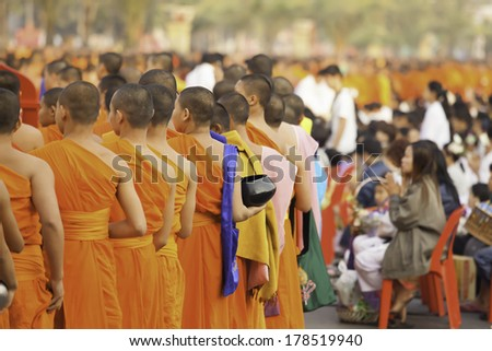 Lampang, THAILAND - SEPTEMBER 23, 2014: people give food and drink for alms to 10,000 Buddhist monks on February 23, 2014 at the Duangratana Lampang, Thailand.