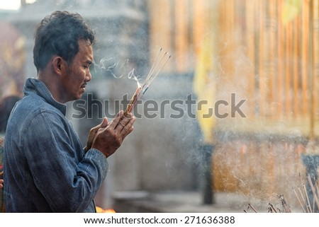 LAMPHUN, THAILAND, DECEMBER 31, 2014: A man holding burning incense sticks is praying for the new year outside the Buddhist temple of Wat Phra That Hariphunchai in Lamphun, Thailand - stock photo