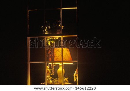 Lamplight in window of home at night in  Bourbon, MO - stock photo