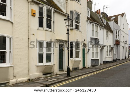 lamppost and old houses at Brighton, foreshortening of  a lamppost and a row of old cottages on an uphill street in touristic sea town,  Brighton, East Sussex  - stock photo