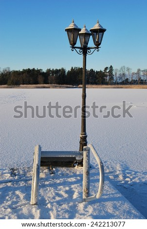 Lamppost at frozen coast