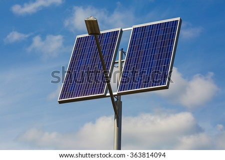 Lamppost with solar panels against a blue sky.  - stock photo