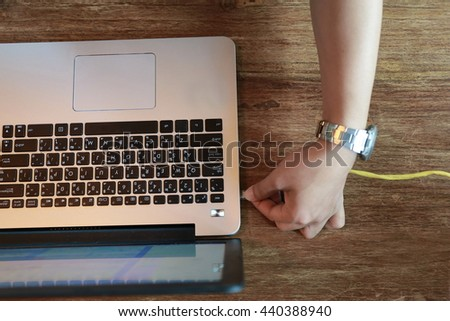 LAN cable is connecting internet to laptop , hand working with laptop, Layout of working place with wooden table and laptop laying,copy space ,Place of work. comfortable working space - stock photo