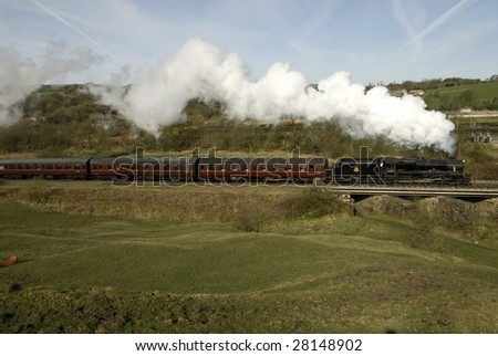 LANCASHIRE, ENGLAND -  APRIL 5 : A British Railway Black 5 class locomotive 45407 crosses the River Irwell, north of Irwell Vale Halt on East Lancashire Railway April 5, 2009 in Lancashire.