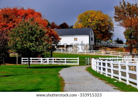 Lancaster, Pennsylvania - October 18, 2015:  White fences, pathways, trees with Autumn foliage, and the Old Farm Equipment Shed-Corn Barn at the Amish Farm and House Museum *