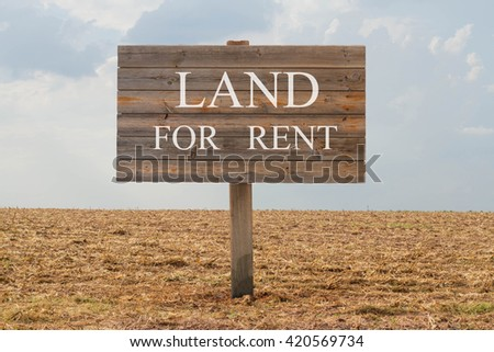 Land for rent - wood board with text on soil background - stock photo