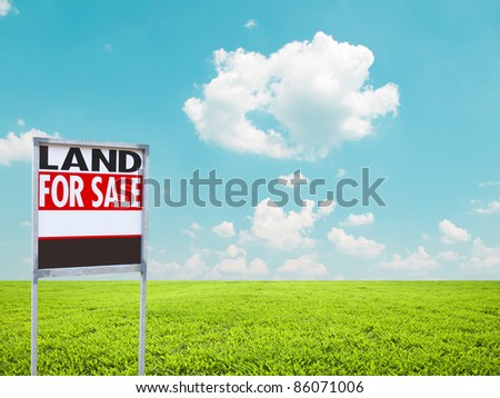 Land for sale sign on empty green field - stock photo