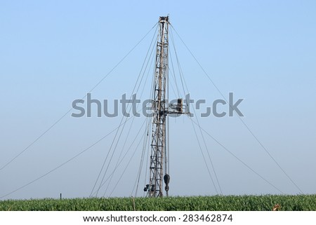 land oil drilling rig behind wheat field - stock photo