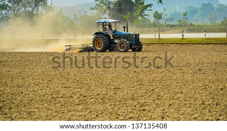 Land preparation with tractor, Tractor plows a field, agriculture modern method. - stock photo