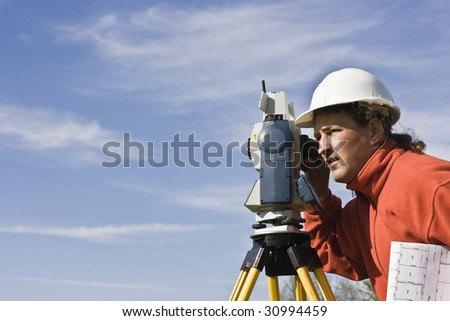 Land Surveying under cloudy sky. - stock photo