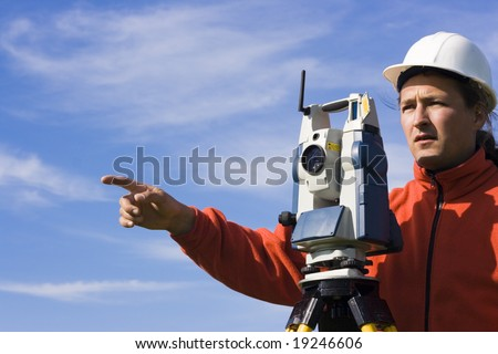 Land Surveyor in the field - spring surveying. - stock photo
