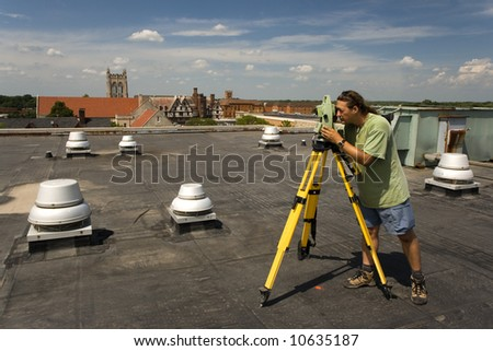 Land surveyor working on the roof - stock photo
