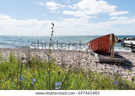 Landed red rowing boat by a colorful beach at the swedish island Oland
