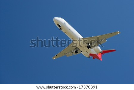 Landing aircraft against clear blue sky - stock photo
