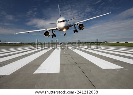 Landing aircraft low over the runway with stretched landing gear - stock photo