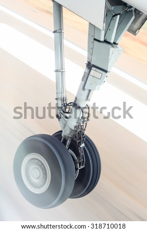 Landing gear during takeoff - The landing gear of an aircraft captured at the moment of takeoff against a blurred runway. - stock photo