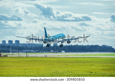 Landing of the passenger plane at hot day time. - stock photo
