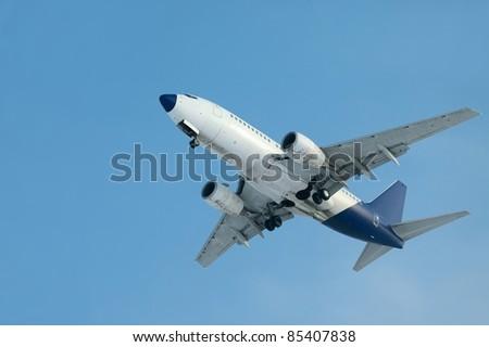 Landing plane against clear blue sky - stock photo