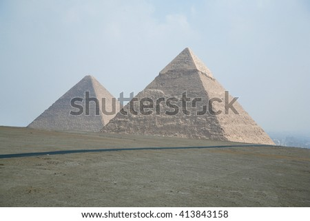 landmark of two pyramids in Giza next to Cairo city Egypt, Africa, the pyramid of Khafre pharaoh and behind the Great Pyramid of Khufu, from year 2500 Before Christ - stock photo