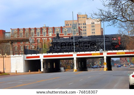 """Landmark train is parked over downtown overpass in Wichita, Kansas.  Train is part of """"Old Town"""" attractions.  Eaton Hotel is seen in background as is traffic lights and traffic. - stock photo"""