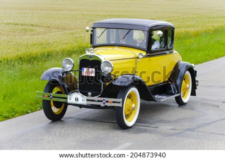 LANDSBERG, GERMANY - JULY 12, 2014: Public oldtimer rally organized by Bavarian city Landsberg for at least 80 years old veteran cars with unknown drivers in Ford A Coupe, built at year 1930 - stock photo