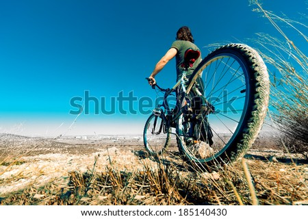 Landscape and young man with mountain bike.Lifestyle and sport - stock photo