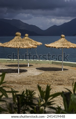 Landscape. April.. Beach with thatched umbrellas before the storm in Marmaris. in Turkey.