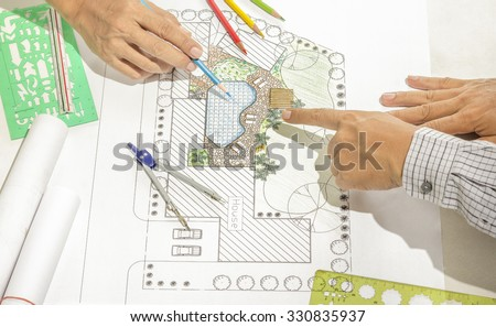 Landscape architect changing drawing at meeting with client
