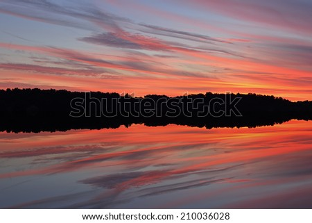 Landscape at twilight, shoreline of West Lake with reflections in calm water, Michigan, USA  - stock photo